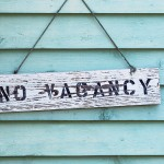 No Vacancy sign hanging on blue or aqua painted cedar siding.